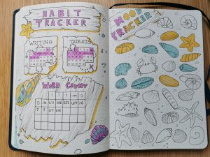 Pax Asteriae's July 2020 bullet journal, showing the habit tracker and mood tracker spreads, with driftwood charts and seashell moods.